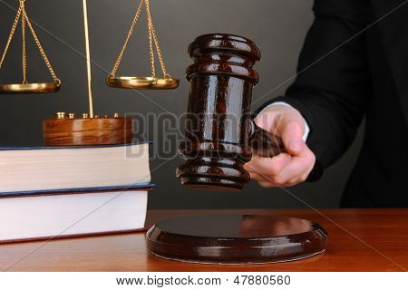 Judge's gavel in hand on grey background