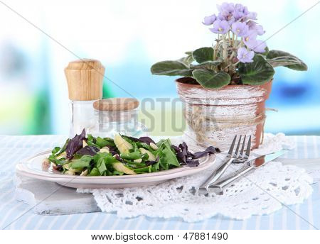 Light salad on plate on table on room background