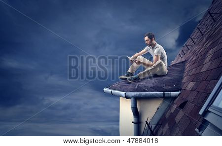 young man with tablet sitting on the roof in the night