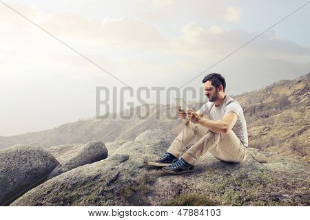young disgusted man sitting on the rocks looking the tablet