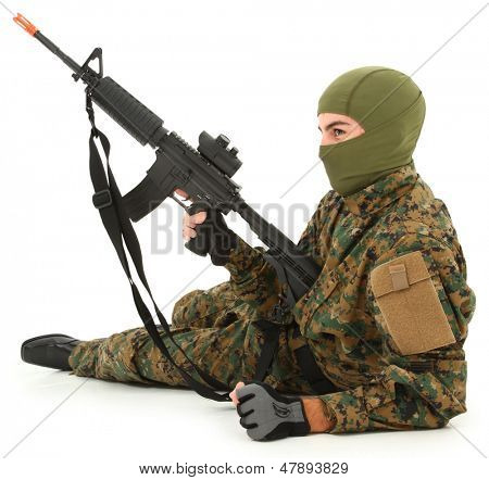 Teen boy in camo gear with air rifle.
