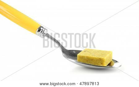 Bouillon cube on spoon, isolated on white