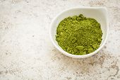 picture of moringa oleifera  - moringa leaf powder in a small bowl against a ceramic tile background - JPG