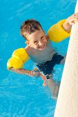 stock photo of floaties  - Smiling boy having a fun at swimming pool with water wings and snorkel - JPG