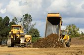 stock photo of dozer  - A large track bulldozer and a large articulating dump truck at a new road project in Oregon - JPG