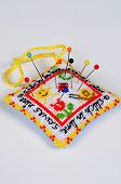 pic of aida  - A stitch in time saves nine pincushion with pins against a plain background - JPG