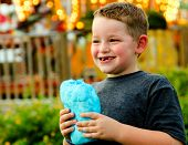 stock photo of candy cotton  - Happy child eating cotton candy at carnival - JPG