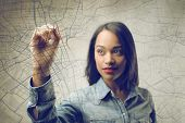 stock photo of orientation  - pretty african woman writing on the map - JPG