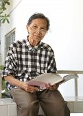stock photo of 70-year-old  - senior woman 70s years old reading book with relaxing emotion - JPG