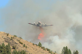 stock photo of retarded  - Large air tanker droping fire retardant at a working natural cover fire near Roseburg Oregon - JPG