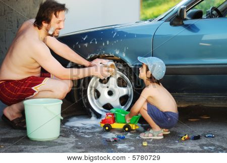 Father And Little Son Are Playing And Washing Car