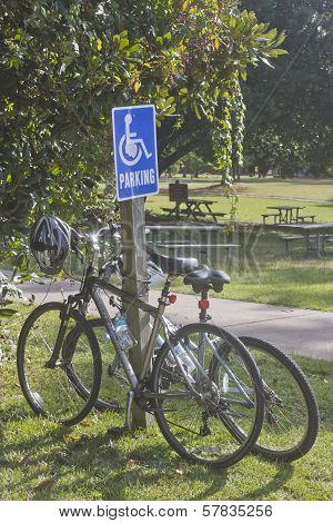Bicycles Chained To A Handicapped Parking Sign