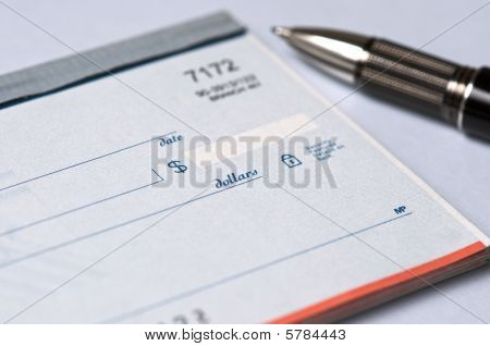 Checkbook on colorful desktop with pen sitting to the side
