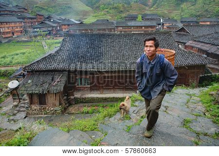 Villager Asian Man Peasant Farmer With A Wicker Basket On His Back.