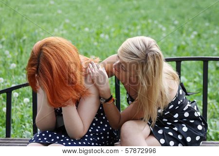 Two Beautiful Girls Sit On Bench And One Consoles Another In Park At Summer Day