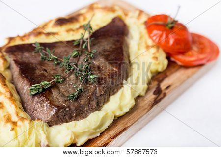 Meat Steak With Potato Puree Backed On Wood Board