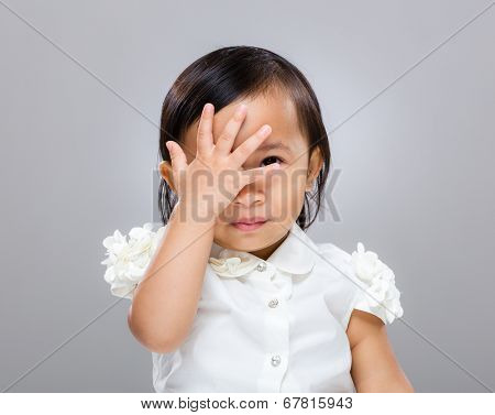 Baby girl with hand cover her face