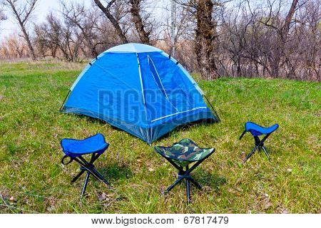Tourist tent with three chairs on green meadow
