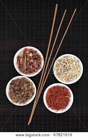 Frankincense, myrrh, sandalwood, pot pourri and incense sticks over bamboo background.