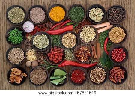 Large herb and spice sampler in wooden bowls and loose over oak wood background.
