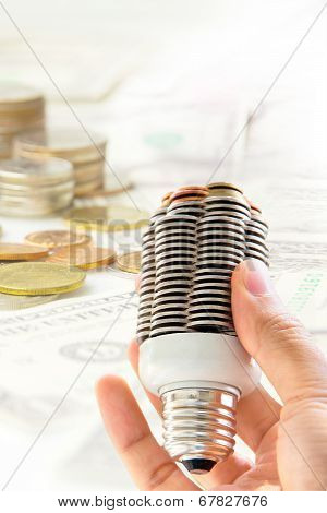 hand holding coin light bulb