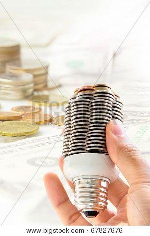 hand holding coin light bulb