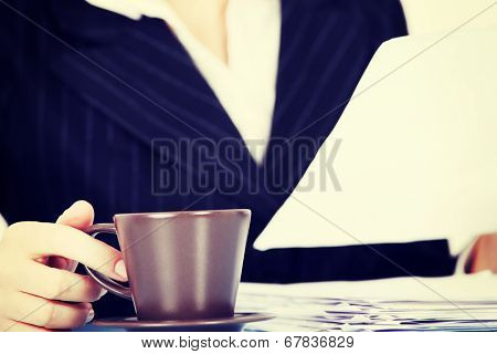 Working business woman with dociments and a cup of coffee or tea.