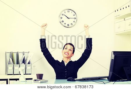 Beautiful business woman rise her hands up. She is happy and satisfacted. Success in work concept.