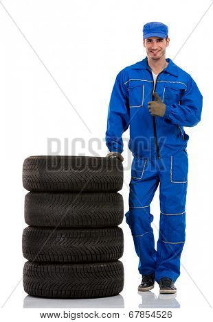 young car mechanic with pile car tires showing thumbs up