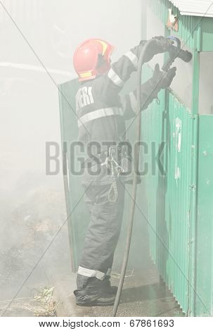 Firefighter in action - Fireman extinguishing a fire