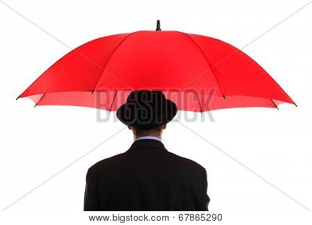 Businessman or insurance agent wearing a bowler hat holding a red umbrella concept for ample insurance cover and business protection