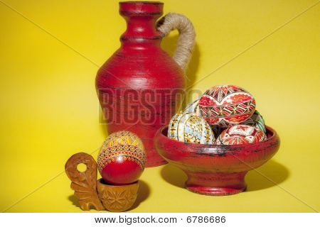 Painted Easter Eggs In Red Pottery Next To Wine Pottery