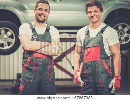 Two servicemen in a car workshop
