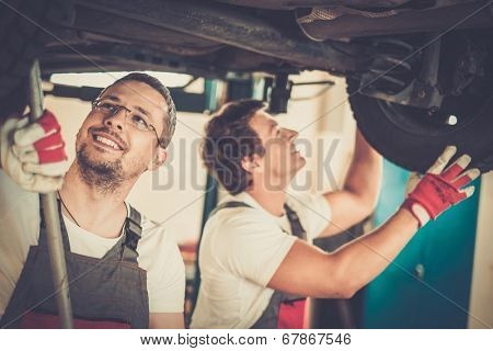 Servicemen checking suspension in a car workshop