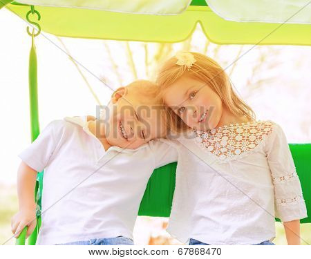 Portrait of two happy kids on swing, enjoying entertainment in summer camp, carefree childhood, active lifestyle, friendly family concept