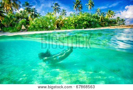 Active female swimming under water, enjoying beautiful sea nature, luxury beach resort on tropical island, summer adventure and journey concept