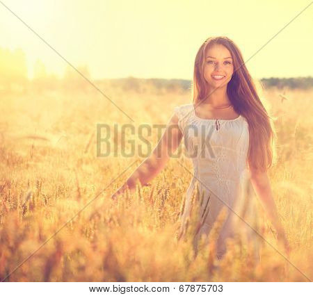 Beauty Girl Outdoors enjoying nature. Beautiful Teenage Model girl in white dress running on the Field, Sun Light. Glow Sun. Free Happy Woman. Toned in warm colors. Summer