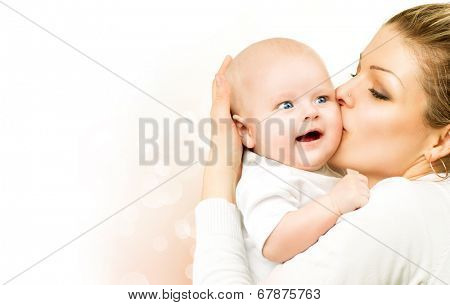 Mother and Baby kissing and hugging. Beautiful mom with her child portrait. Happy Family isolated on a white background. Parenthood, motherhood concept
