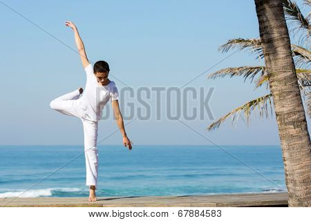 energetic young female dancer dancing on the beach