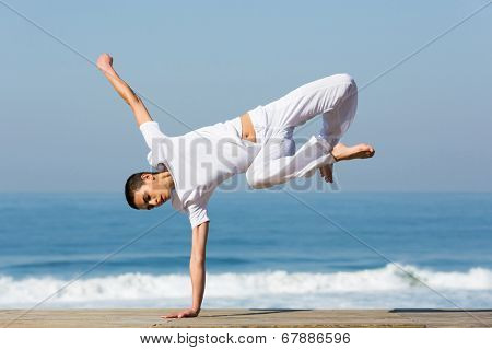 female dancer practicing handstand on beach