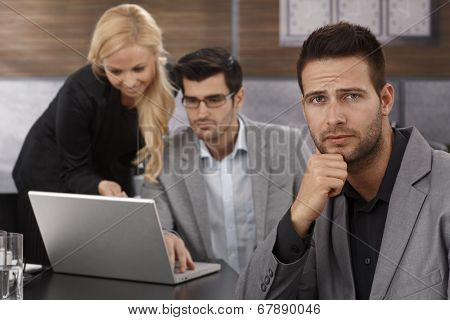 Troubled businessman sitting in office, looking troubled, frowning while colleagues working at background.