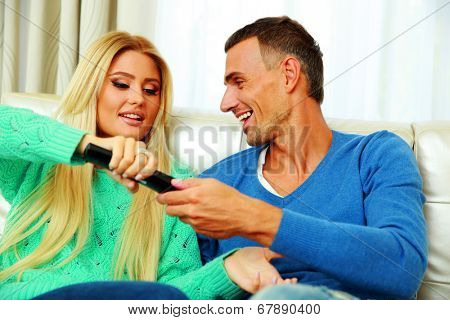 Happy couple bickering to change tv channel on remote control