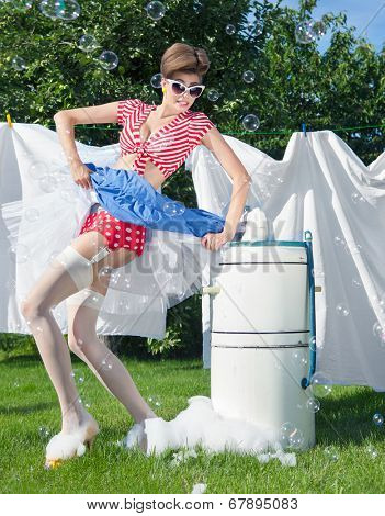 Skirt caught by wringer, pin up style photo of woman with vintage washing machine doing laundry outdoor