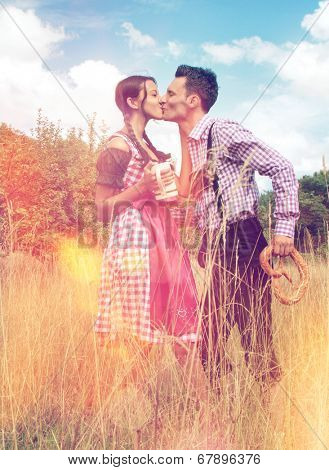 Loving Bavarian couple kissing each other in nature whilst holding a beer mug and brezel