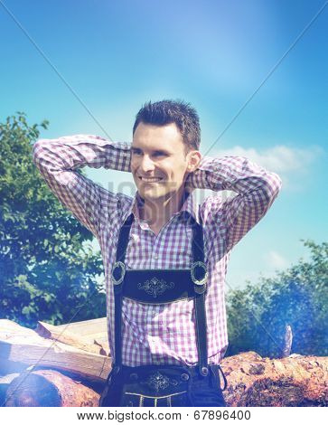 Handsome guy wears a Lederhosen and poses outside in nature
