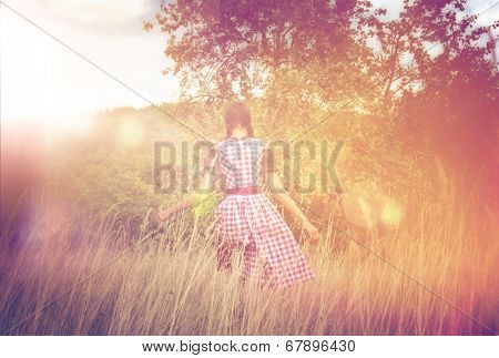 Rear view of young woman in Bavarian dirndl walking alone in the field