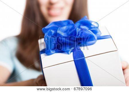 Smiling woman hand holding blue ribbon wrapped holiday surprise gift or present box package