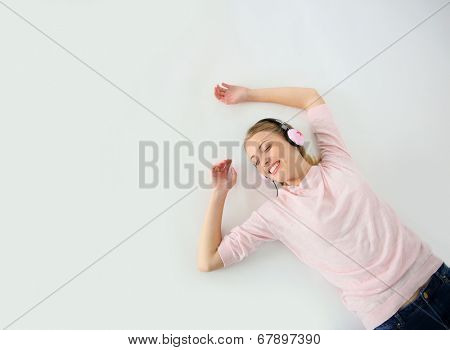 Blond girl relaxing on floor with headphones on, isolated,
