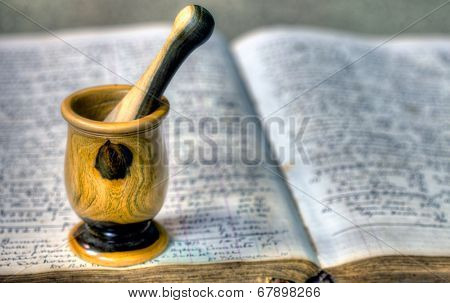 Old pharmacy book with mortar and pestle
