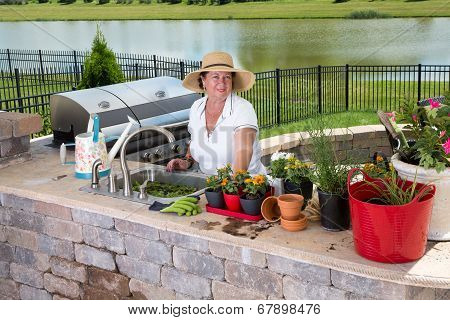 Attractive Senior Woman Caring For Her Pot Plants